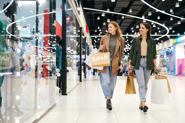 Happy attractive girls in casual outfits walking over mall and enjoying shopping together
