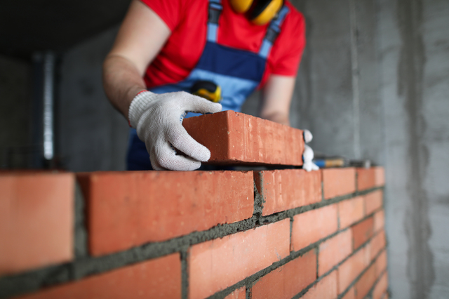 Builder makes a brickwork of a wall in an apartment. A man in uniform lays a brick on cement. Construction of a residential complex